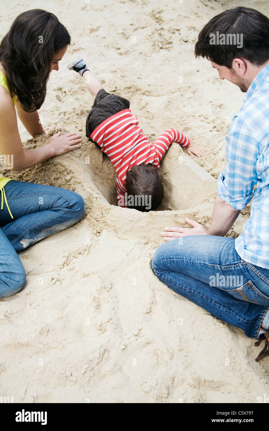 Germany, Berlin, Family and son (3-4) playing in sandbox - Stock Image