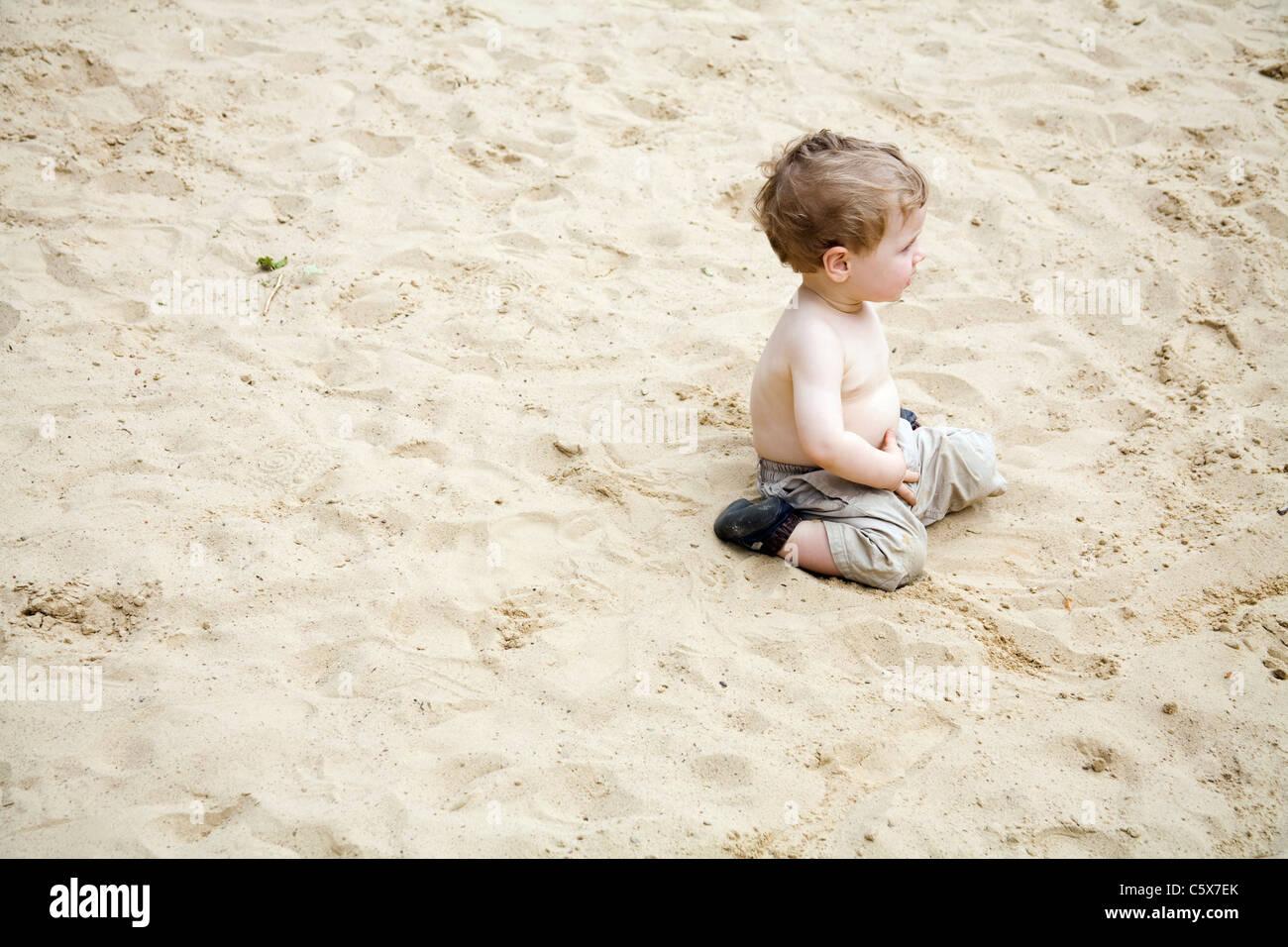 Germany, Berlin, Boy (2-3) sitting in sandbox - Stock Image