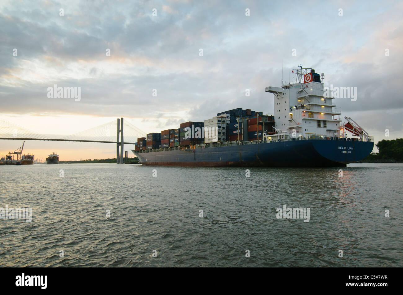 A cargo ship navagates to pass under the Talmadge Memorial Bridge in Savannah, Georgia at sunset. - Stock Image
