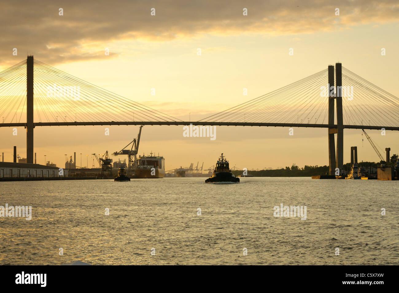 A tug boat passes under the Talmadge Memorial Bridge in Savannah, Georgia at sunset. - Stock Image