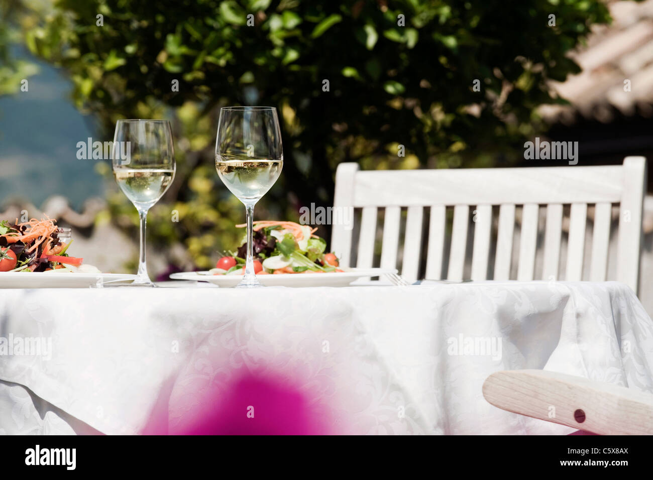Italy, South Tyrol, Laid table, with mixed salad on plates and two glasses with white wine - Stock Image