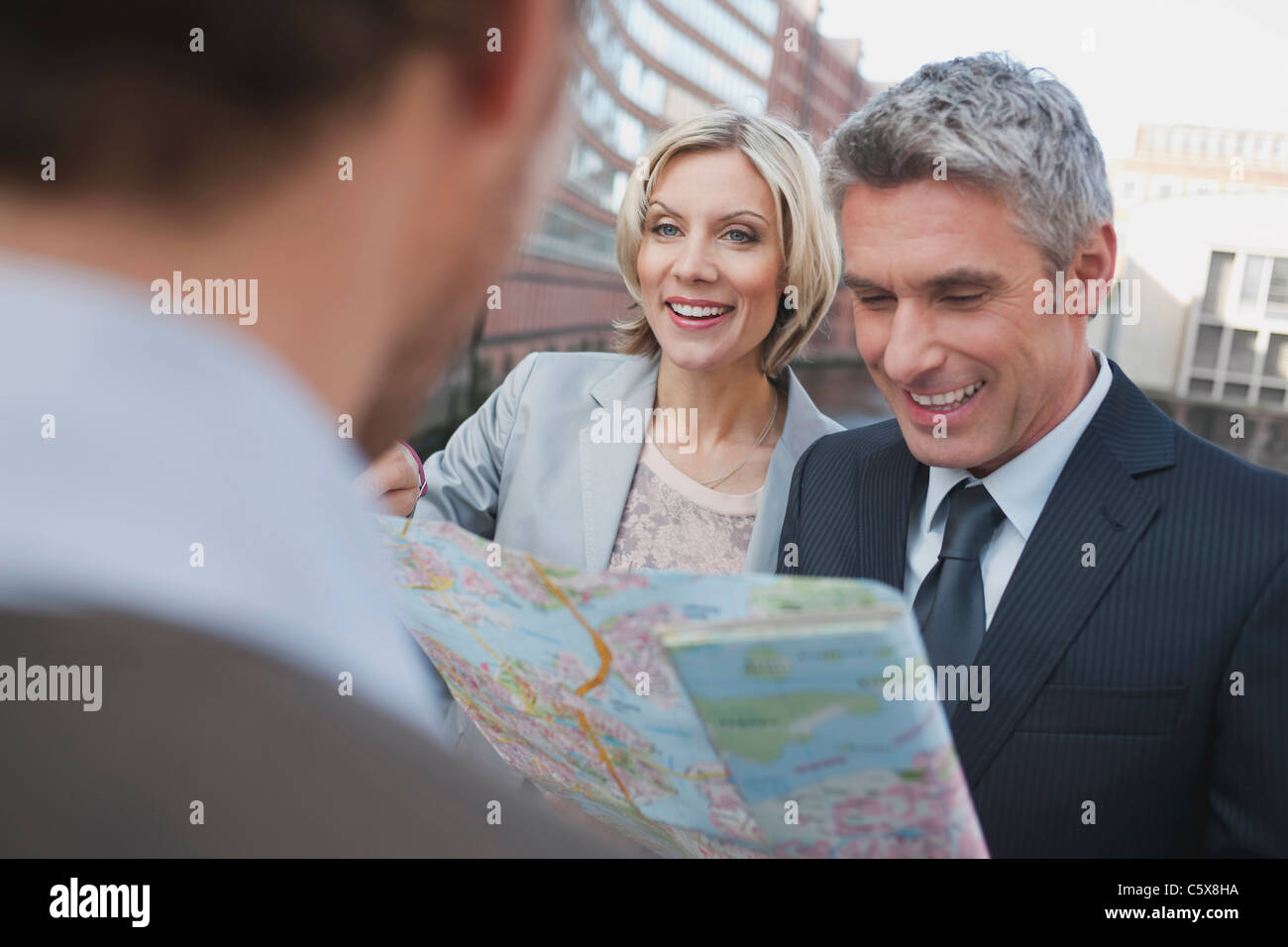 Germany, Hamburg, Business people holding city map, smiling, portrait Stock Photo