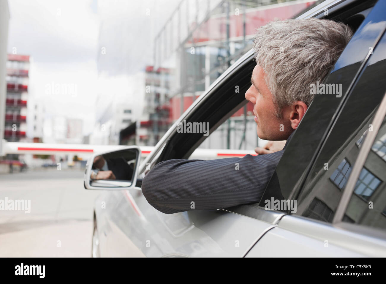 Germany, Hamburg, Businessman sitting in car in front of closed barrier - Stock Image