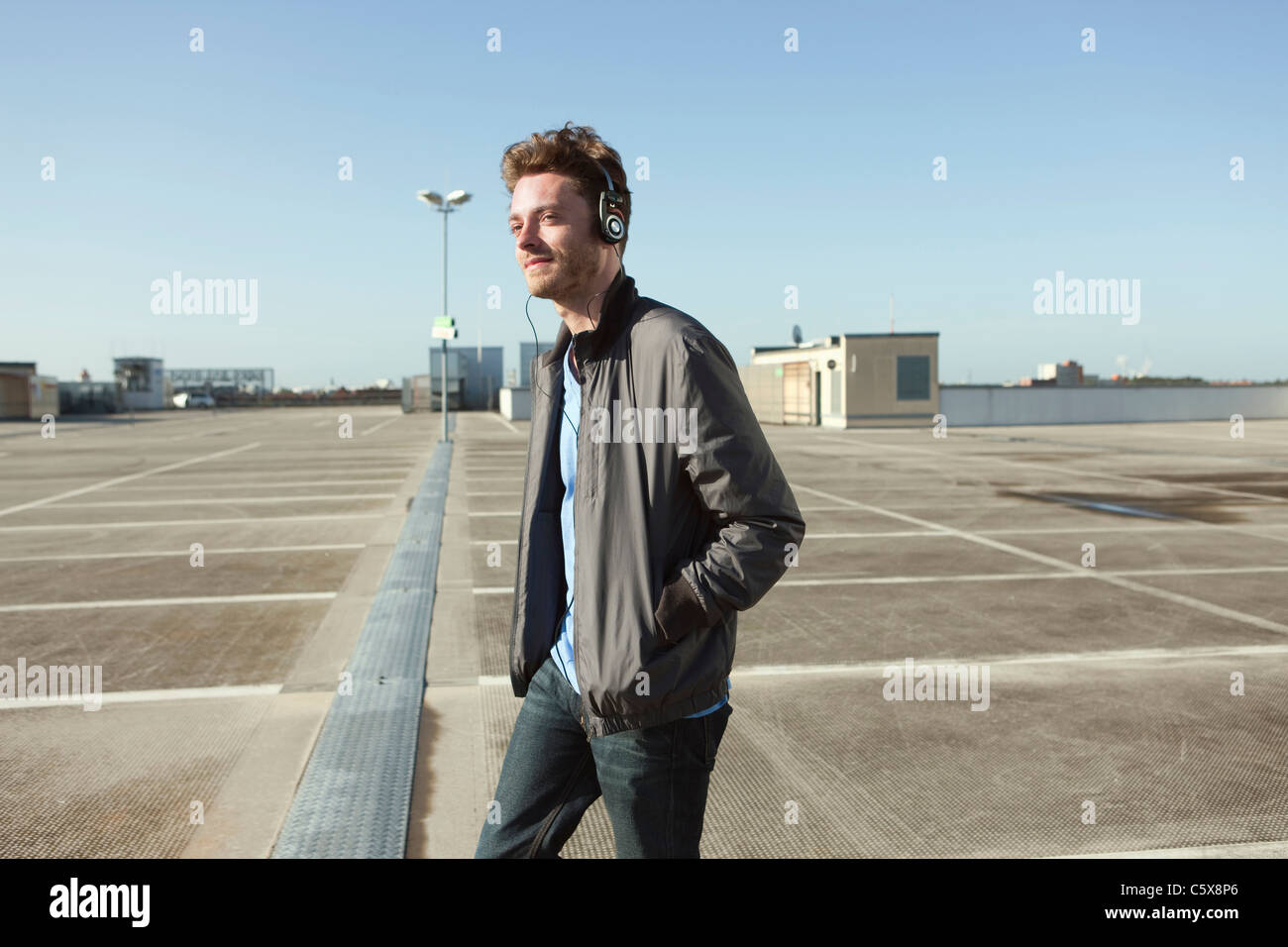 Germany, Berlin, Young man on deserted parking level wearing headphones - Stock Image