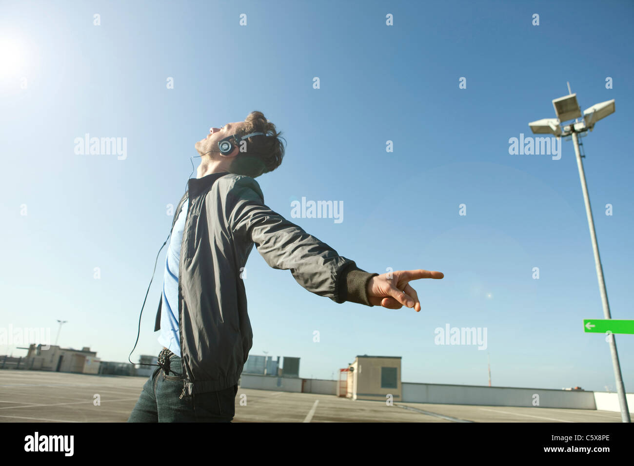 Germany, Berlin, Young man on deserted parking level wearing headphones listening to music - Stock Image