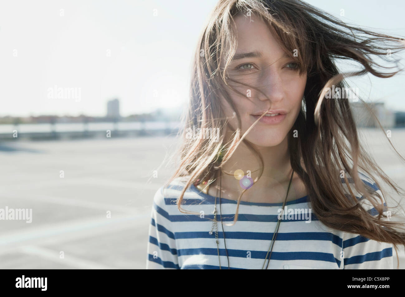 Germany, Berlin, Young woman on deserted parking level, portrait, close-up - Stock Image