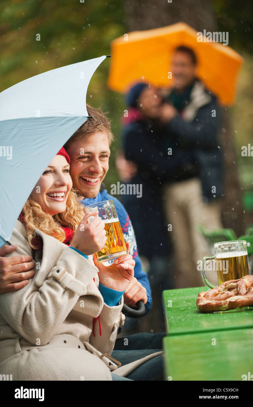 Germany, Bavaria, English Garden, Four persons in rainy beer garden, woman holding beer mug, smiling, portrait - Stock Image