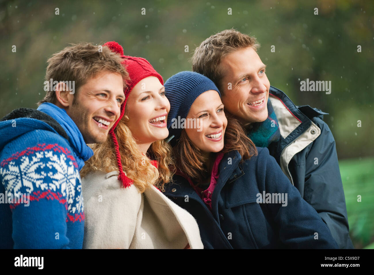 Germany, Bavaria, English Garden, Four persons laughing, portrait, close-up - Stock Image