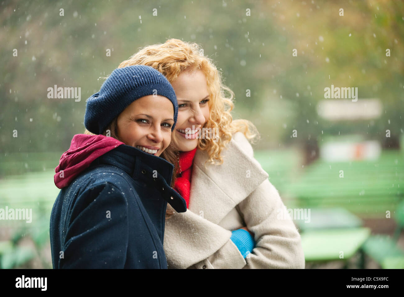 Germany, Bavaria, English Garden, Two women in beer garden, laughing, portrait - Stock Image
