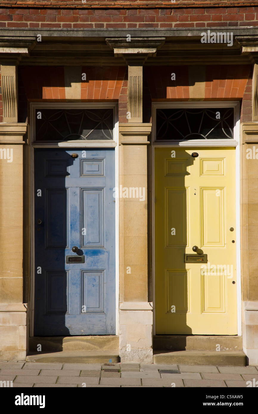 Neighbouring front doors, one is immaculately painted the other less so - Stock Image