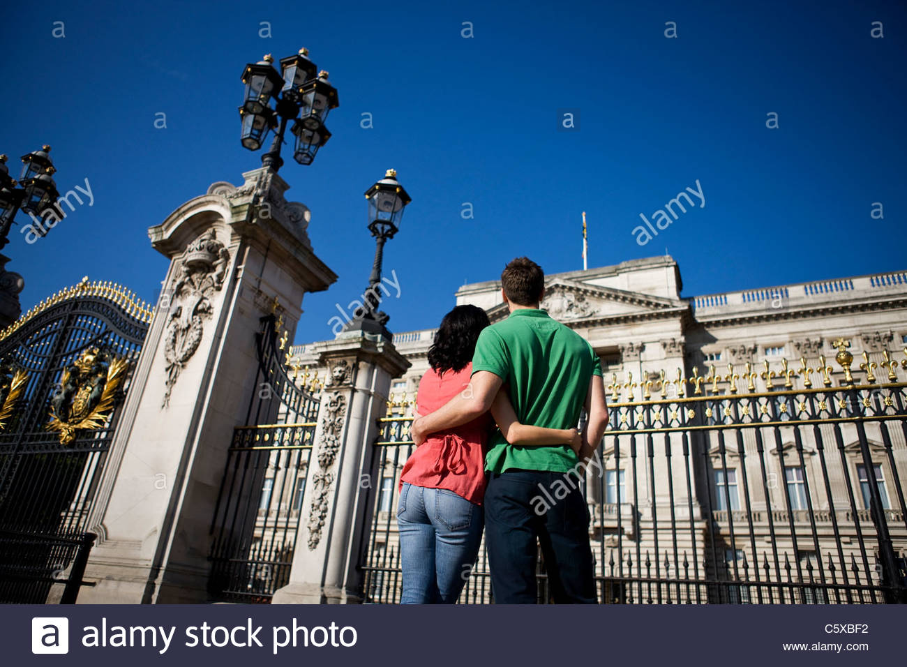 A young couple standing in front of Buckingham Palace, rear view - Stock Image