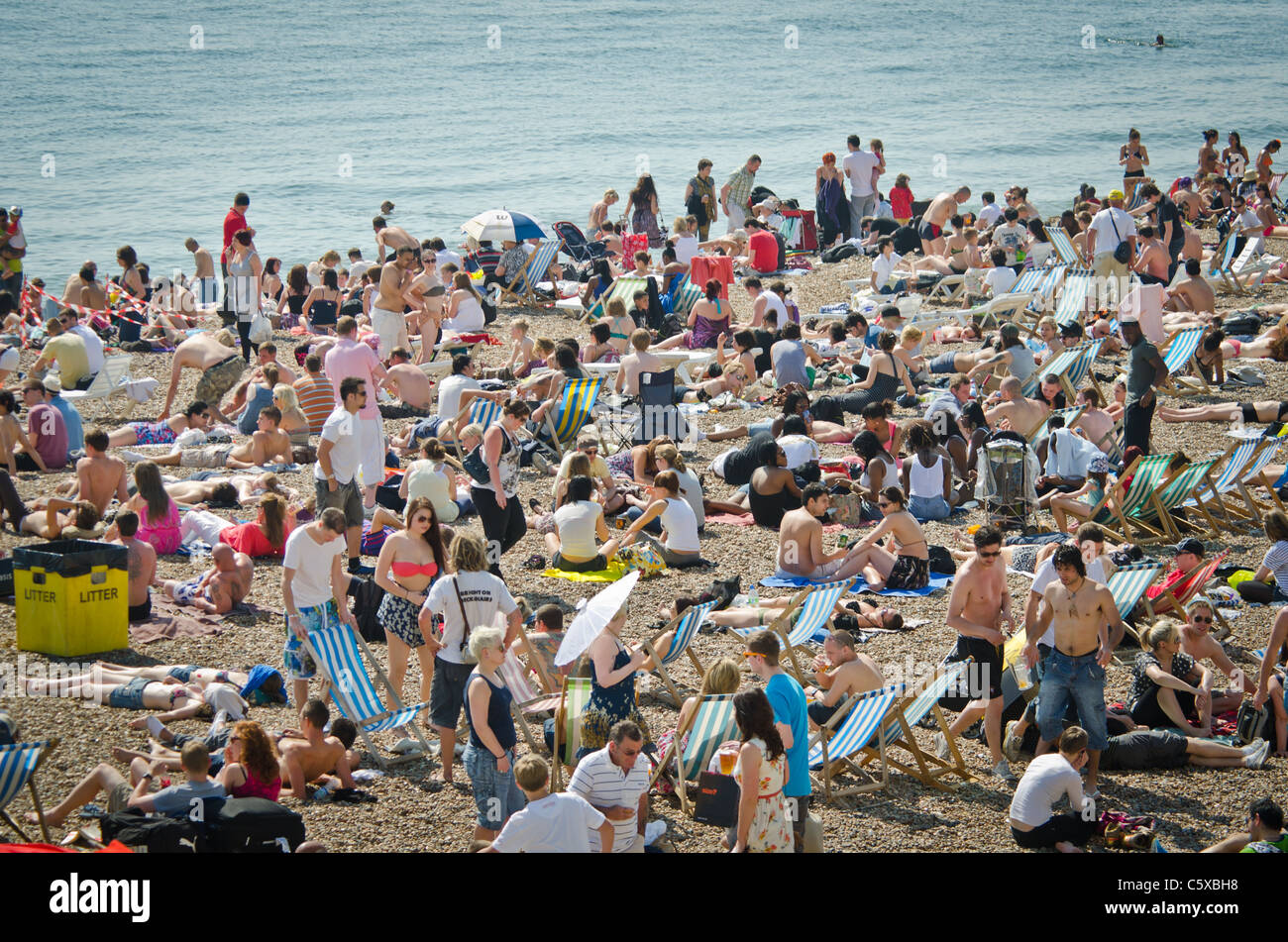 Holiday makers take to Brighton Beach for the hottest Easter on record. - Stock Image
