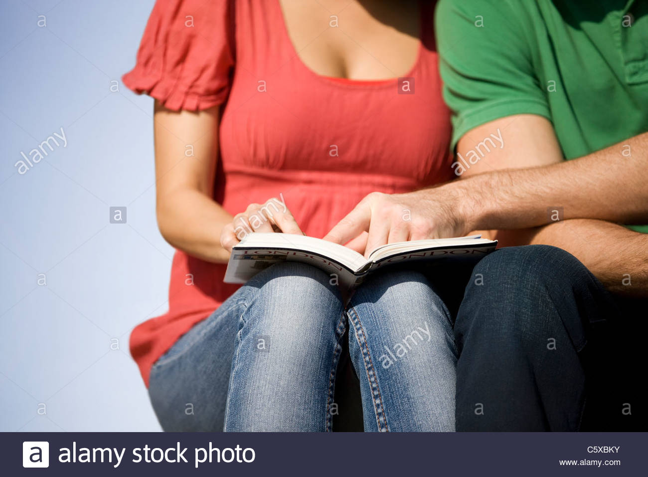 A young couple sitting, reading a guidebook - Stock Image