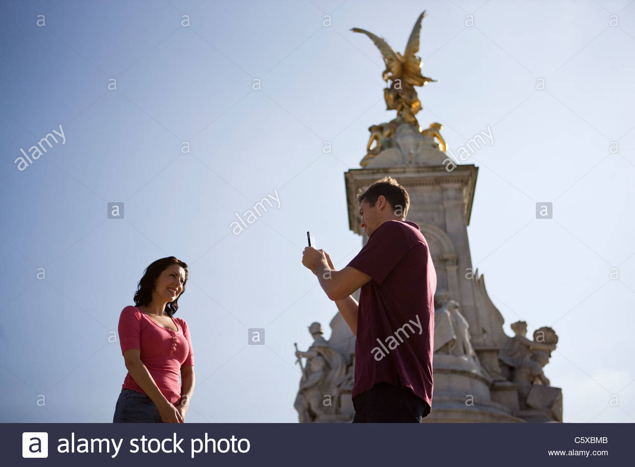 A young man taking a picture of his girlfriend in front of the Victoria Memorial - Stock Image