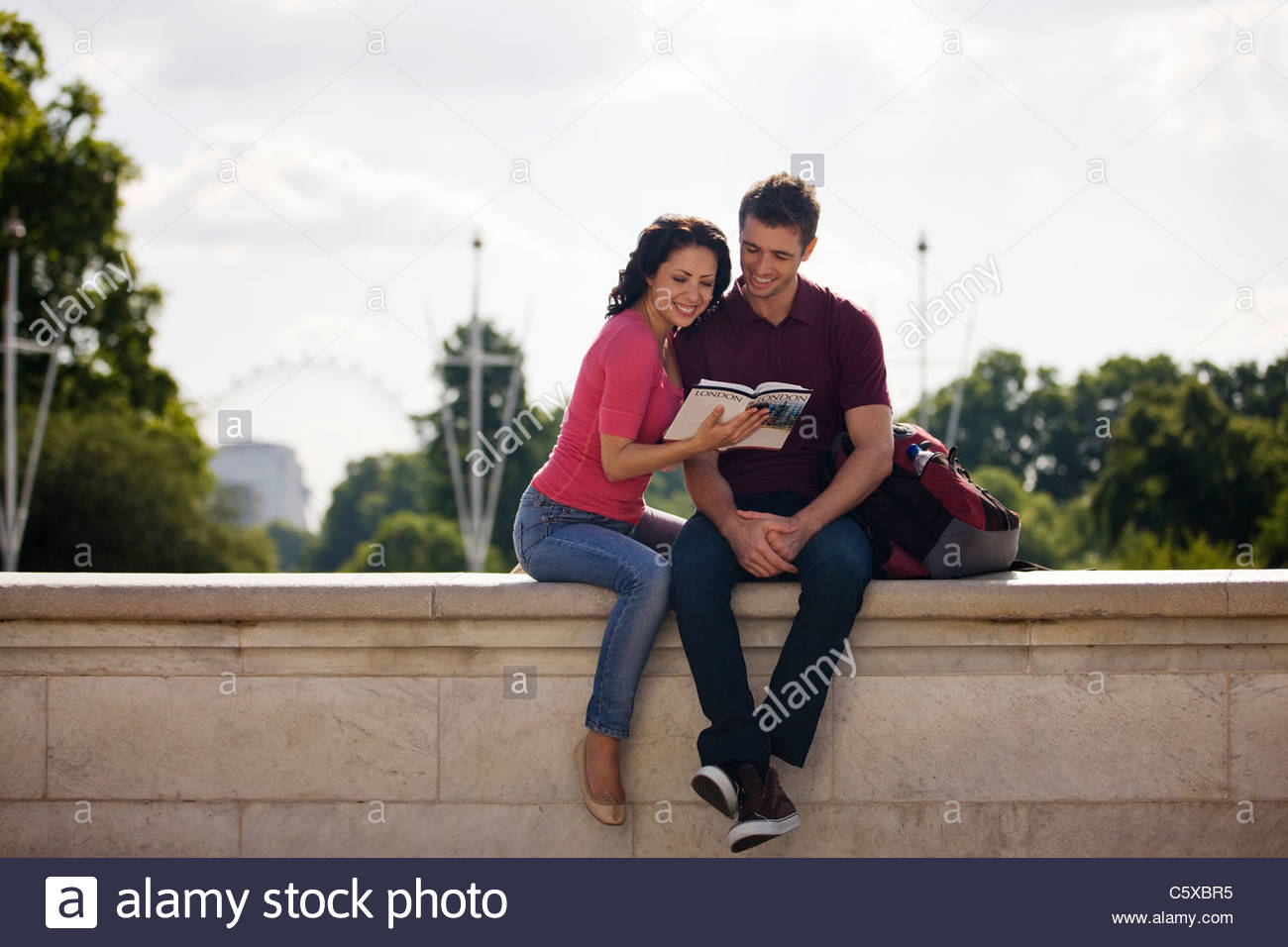 A young couple sitting on a wall, reading a guidebook - Stock Image