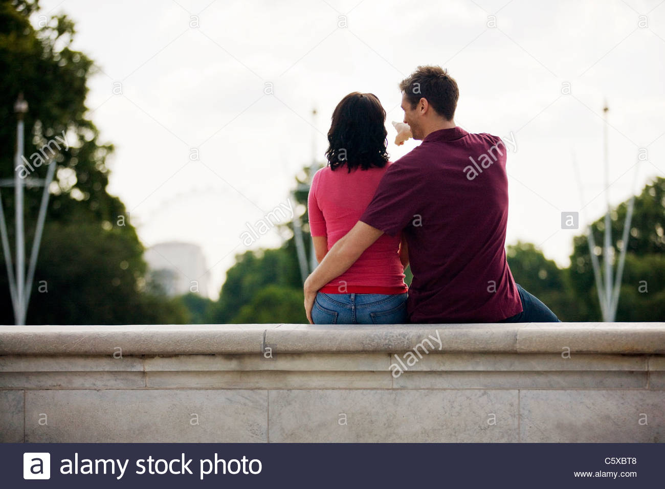 A young couple sitting on a wall, young man pointing at the London Eye - Stock Image