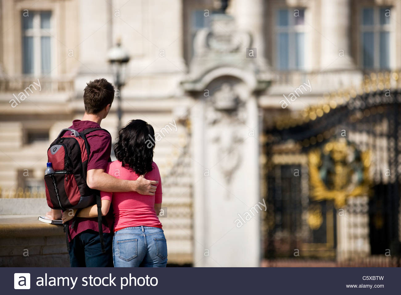A young couple standing in front of Buckingham Palace - Stock Image