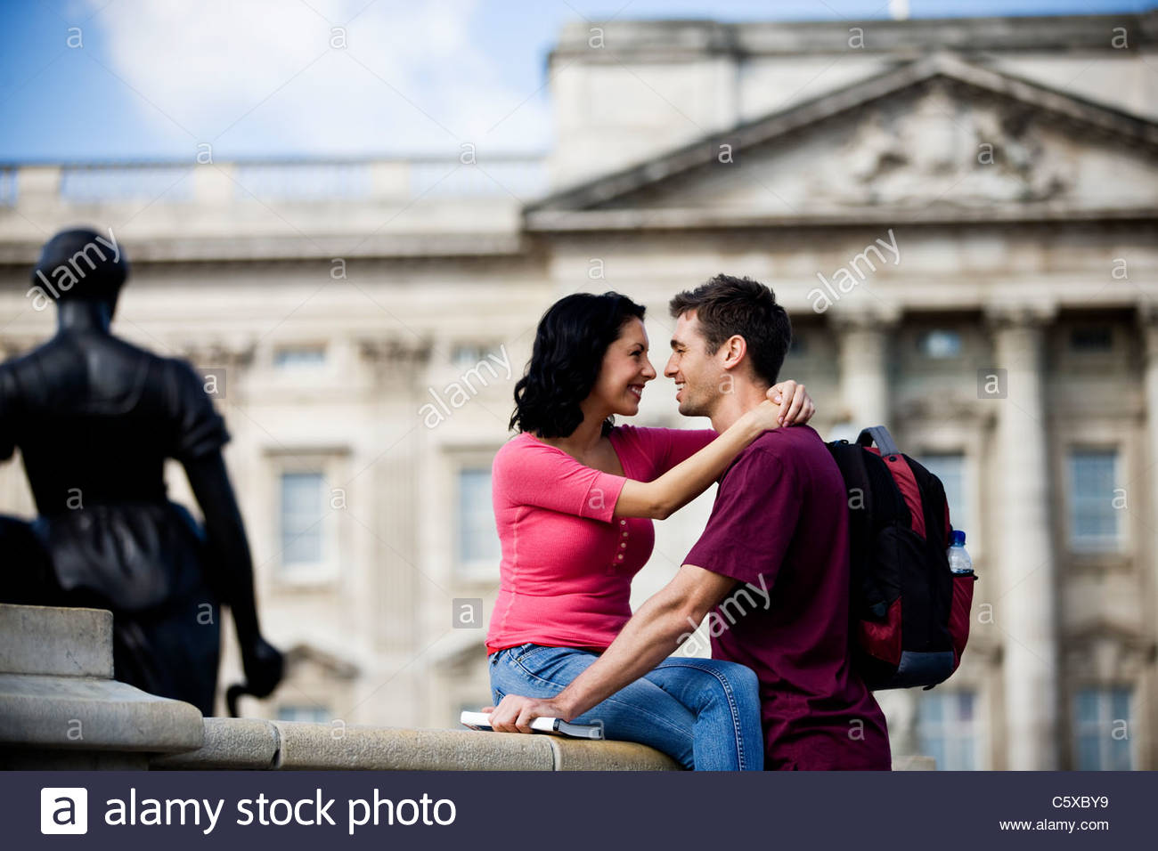 A young couple in front of Buckingham Palace, looking at each other - Stock Image