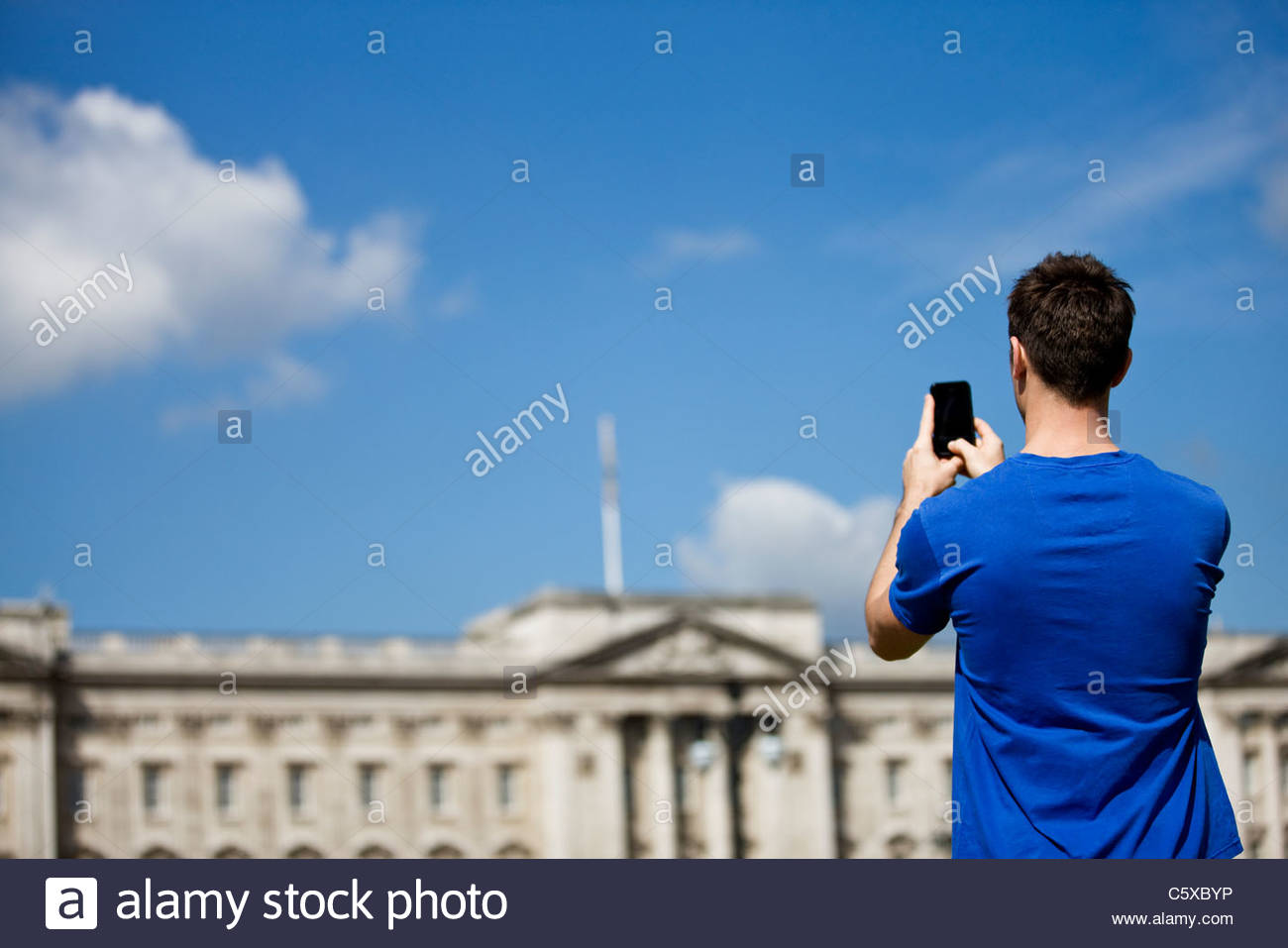 A young man taking a picture of Buckingham Palace - Stock Image