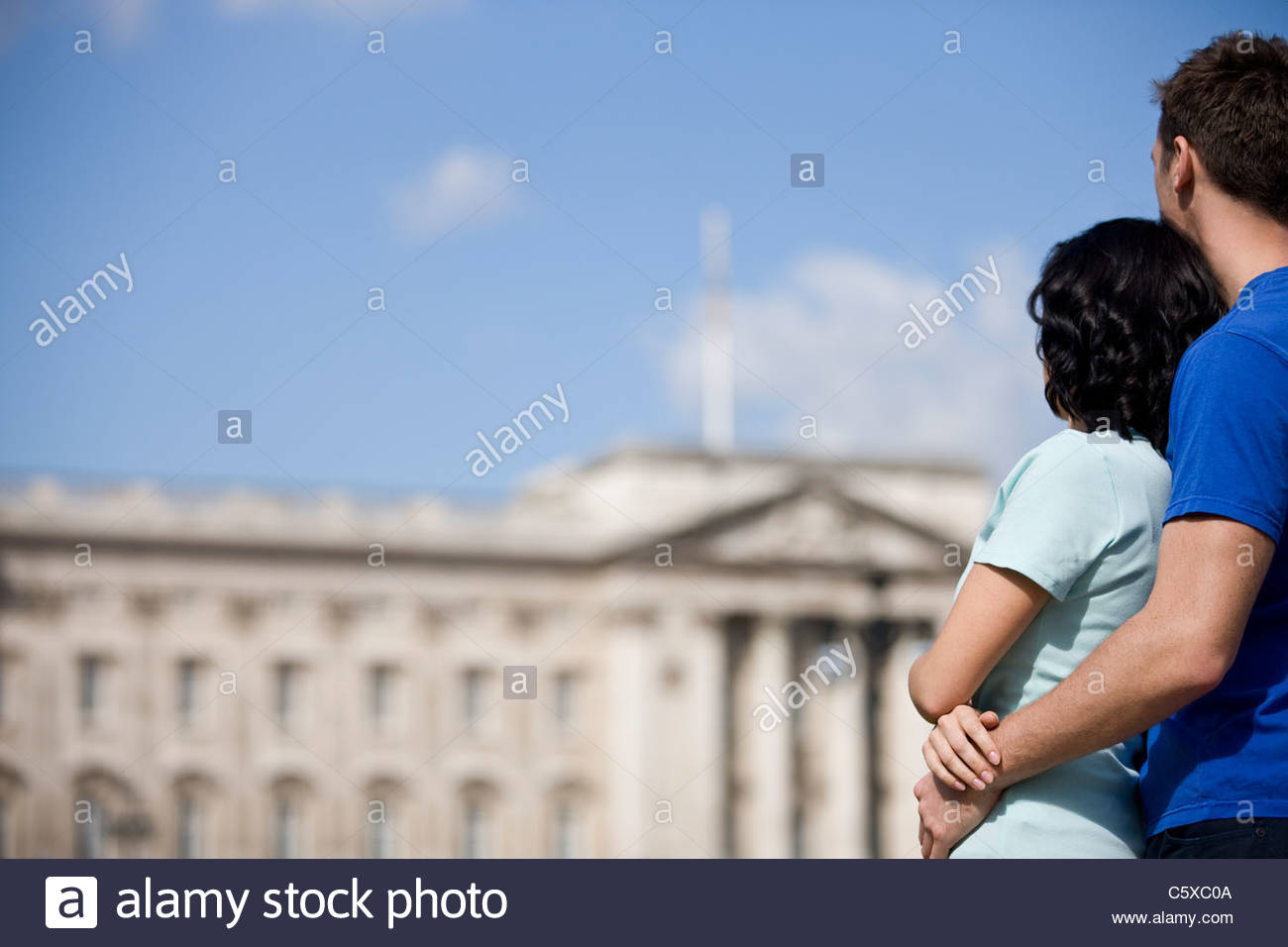 A young couple looking at Buckingham Palace - Stock Image