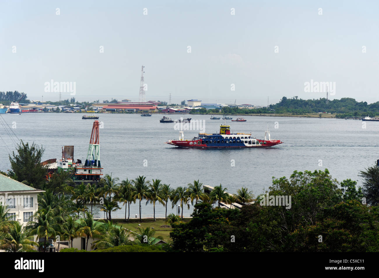 A ferry passing shipping and boats in Labuan, Malaysia - Stock Image