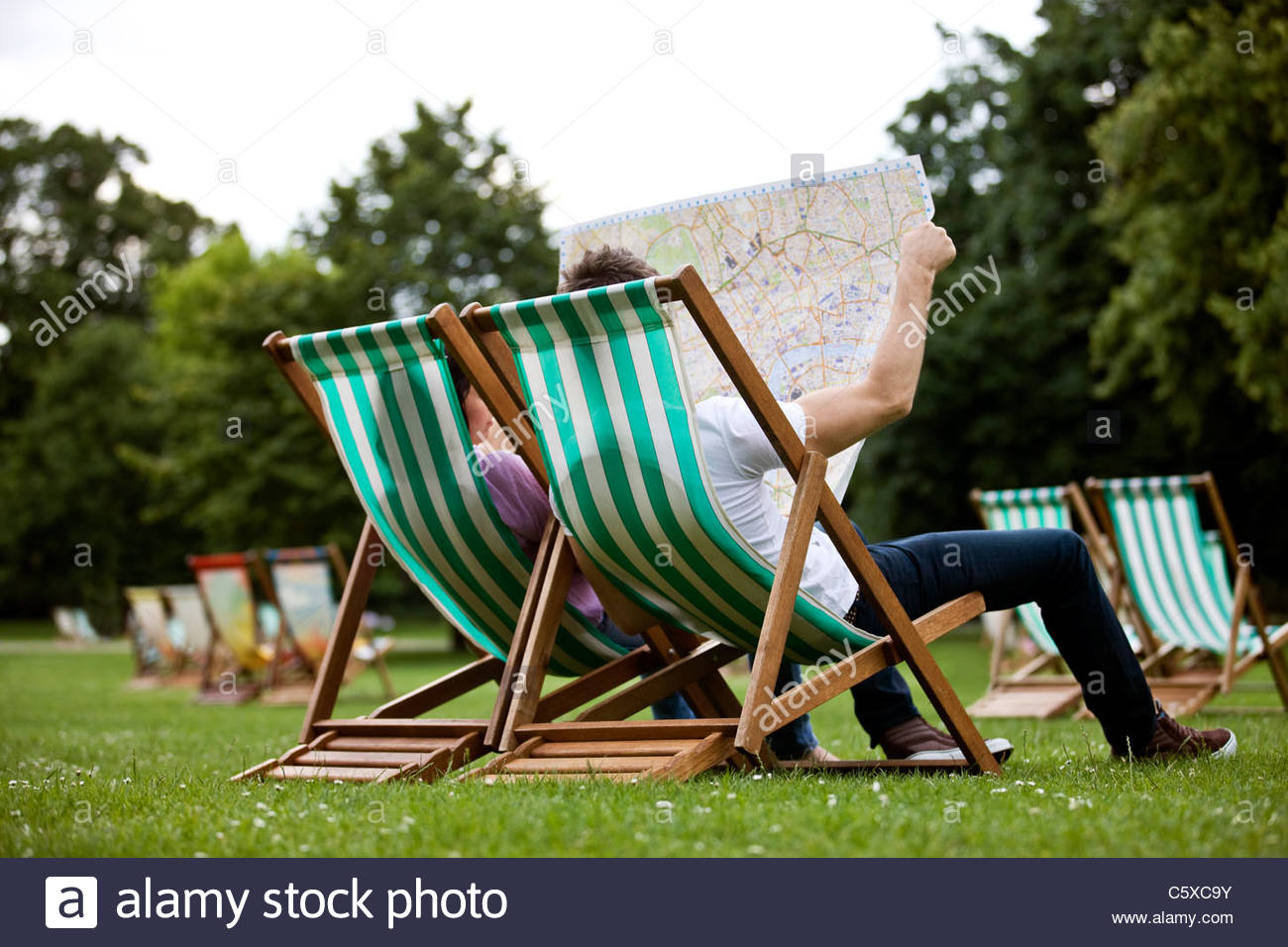 A young couple sitting on deck chairs in St James Park, looking at a map - Stock Image