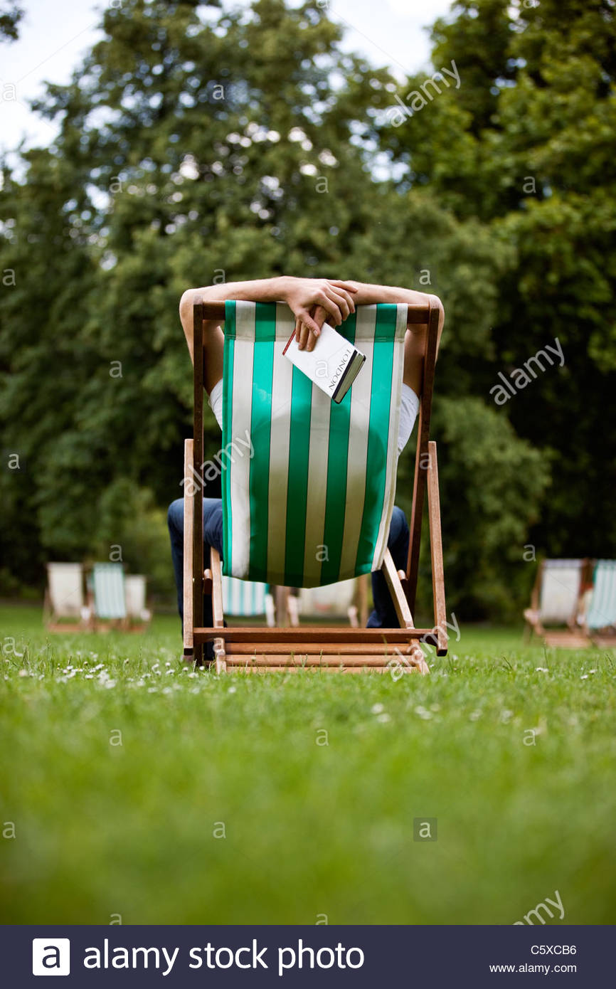 A young man relaxing on a deckchair in St James Park, holding a guidebook - Stock Image