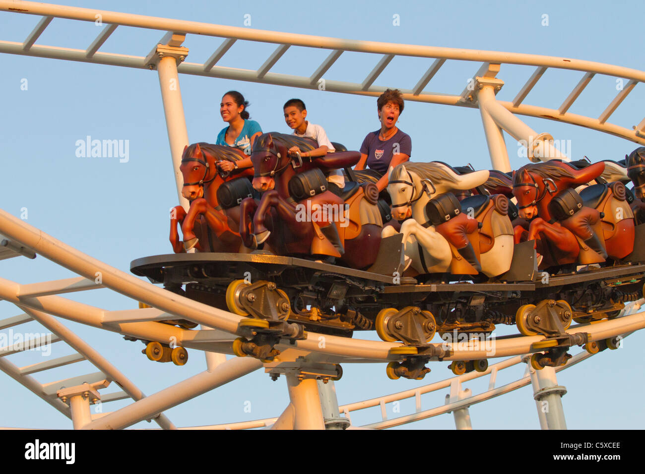 Visitors enjoy the new Steeplechase Ride at Luna Park as the sun sets over Coney Island Stock Photo