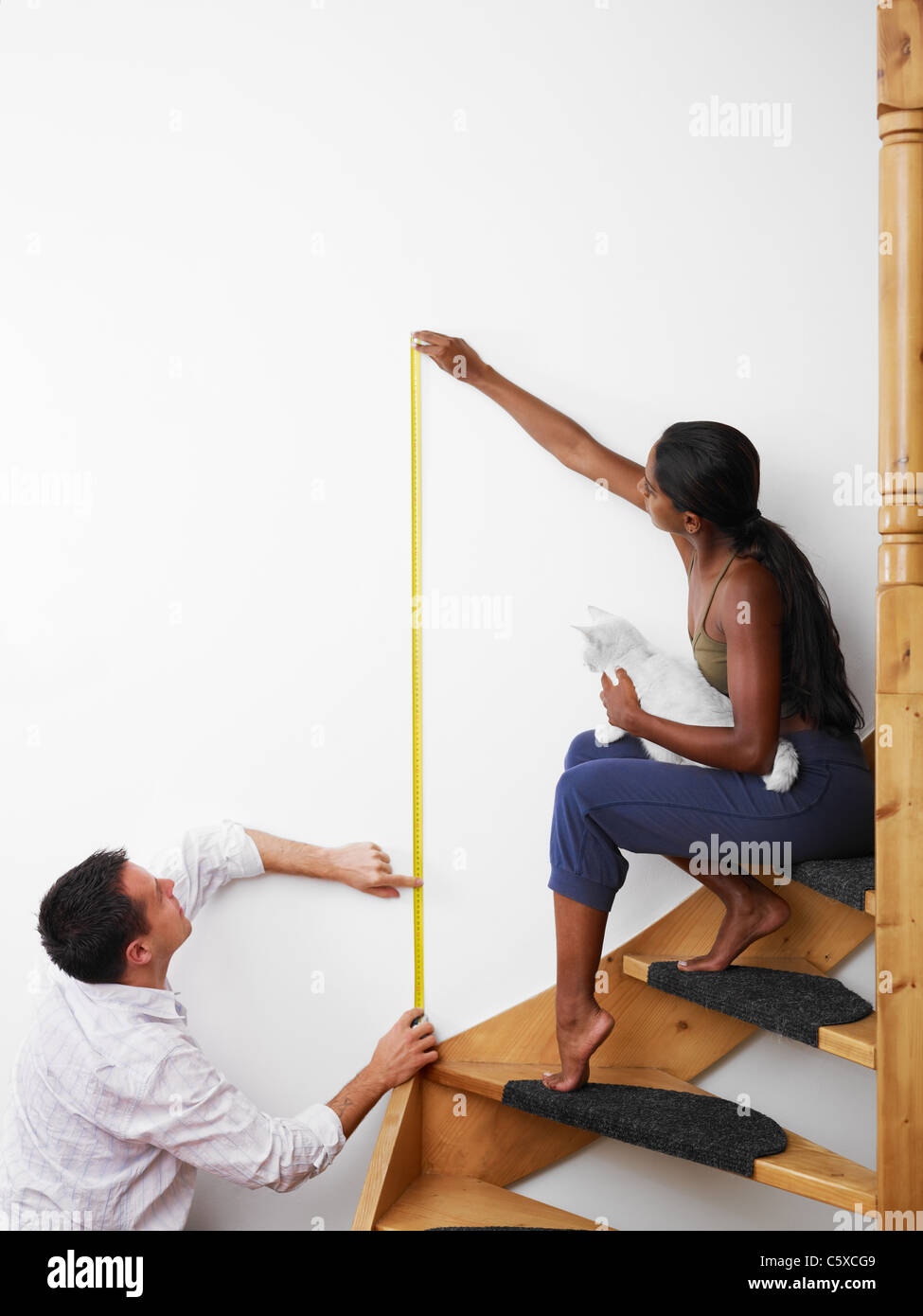Do it yourself: couple measuring wall to hang picture at home. Vertical shape, copy space - Stock Image