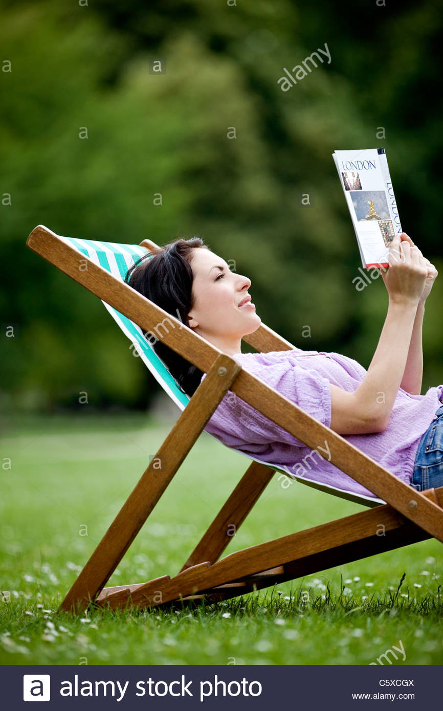 A young woman sitting on a deckchair in St James Park, looking at a guidebook - Stock Image