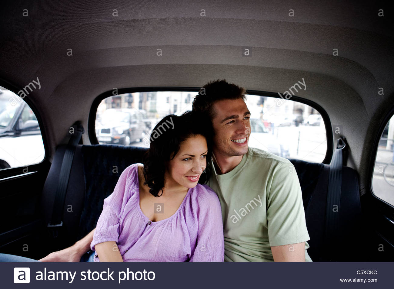 A young couple in a London taxi, admiring the view - Stock Image