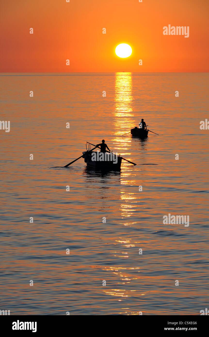 Fisherman on beautiful calm bay at sunrise, Adriatic coast, Italy - Stock Image
