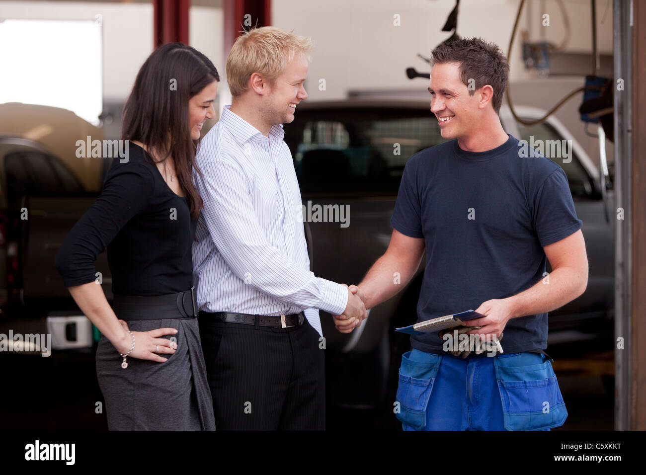 A happy attractive mechanic shaking hands with a customer couple,happy with their service Stock Photo
