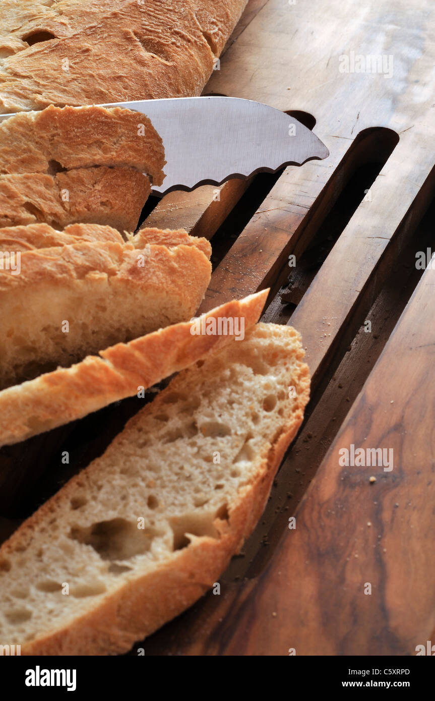 Cutting slices from bread loaf - Stock Image
