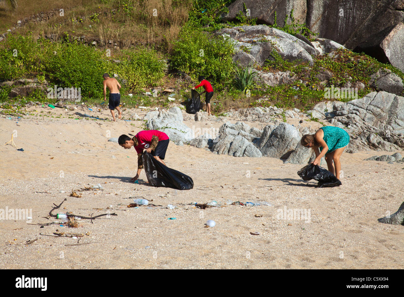 Thai schoolchildren schoolclass and volunteers cleaning Paradise Beach. - Stock Image
