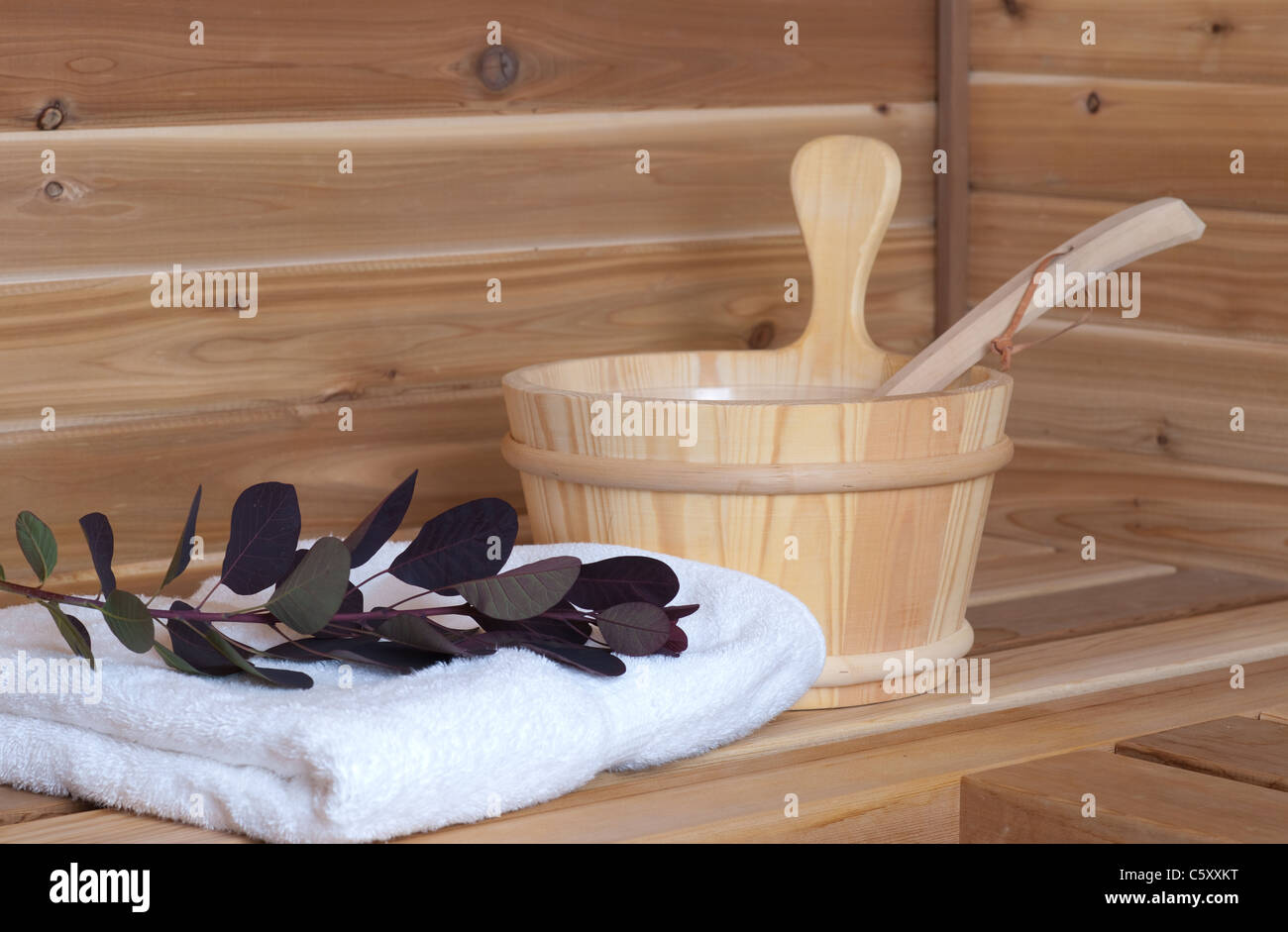 wooden sauna with bucket and ladle beside towel and flower - Stock Image