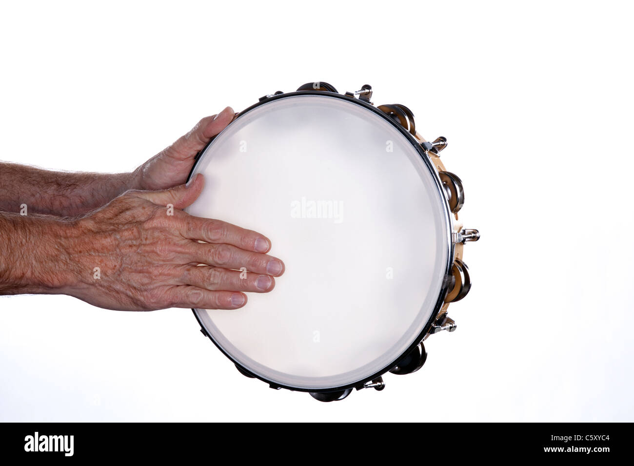 A tambourine being played by a man's hands isolated against a white background. - Stock Image