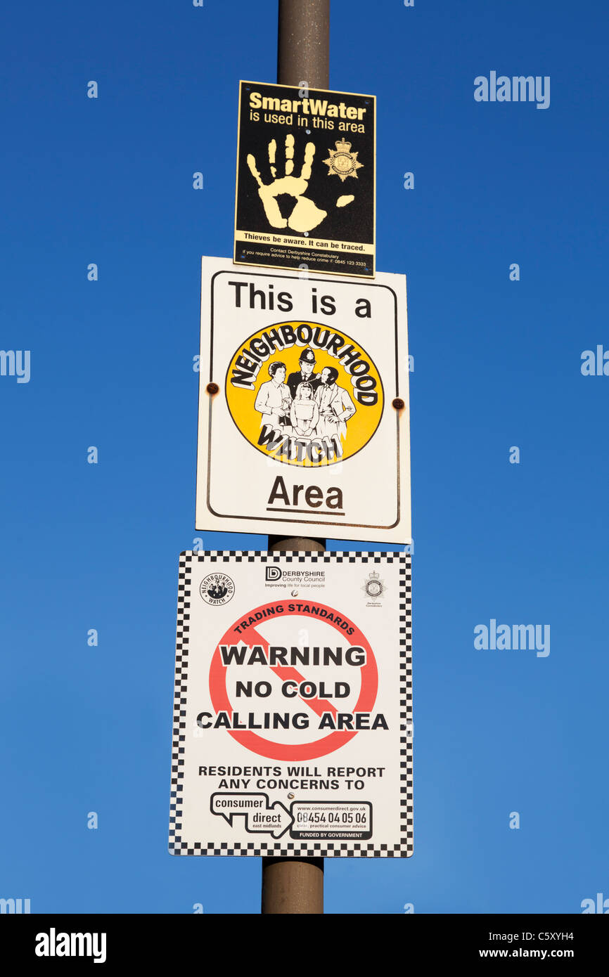 smartwater neighbourhood watch and no cold calling signs on lampost against a blue sky - Stock Image