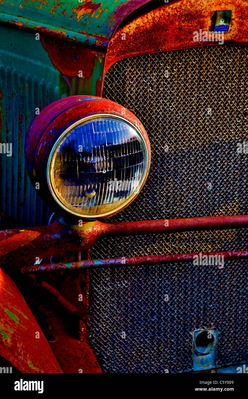 A close up color enhanced image of an antique Plymouth automobile rusting away in a junk yard - Stock Image