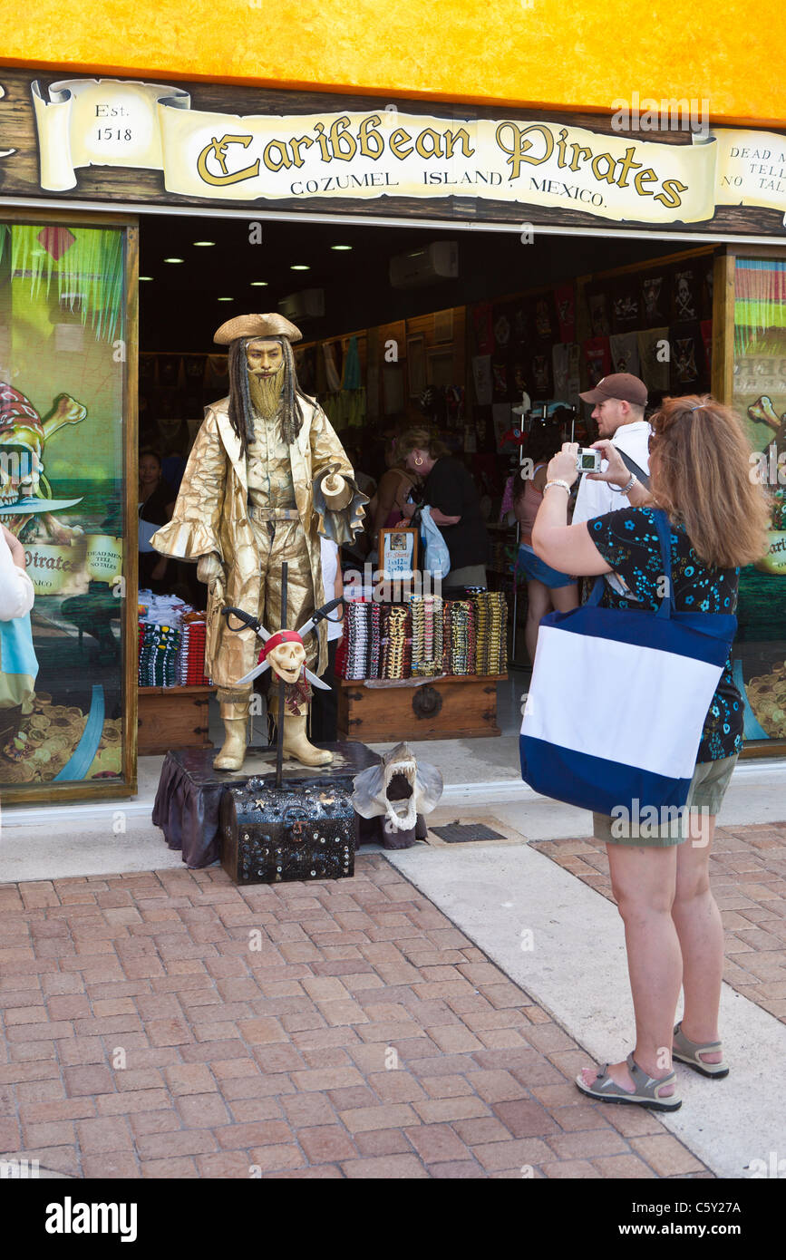 Woman taking picture of mime dressed as a pirate and painted gold outside shop in Cozumel, Mexico in the Caribbean - Stock Image