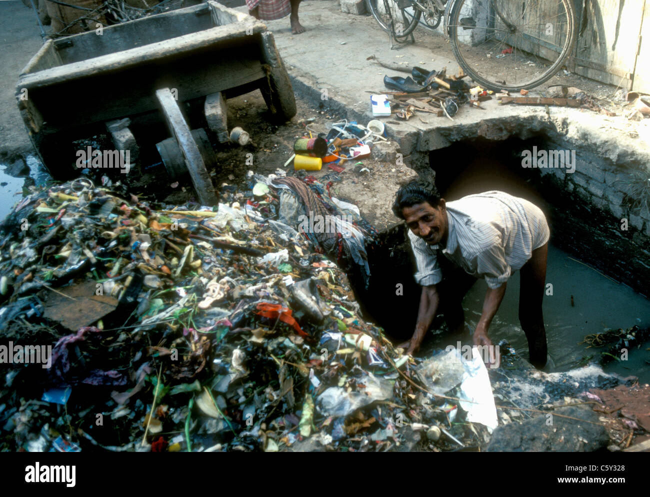 Dallit untouchable man searching for useful items to sell in a drain in India - Stock Image