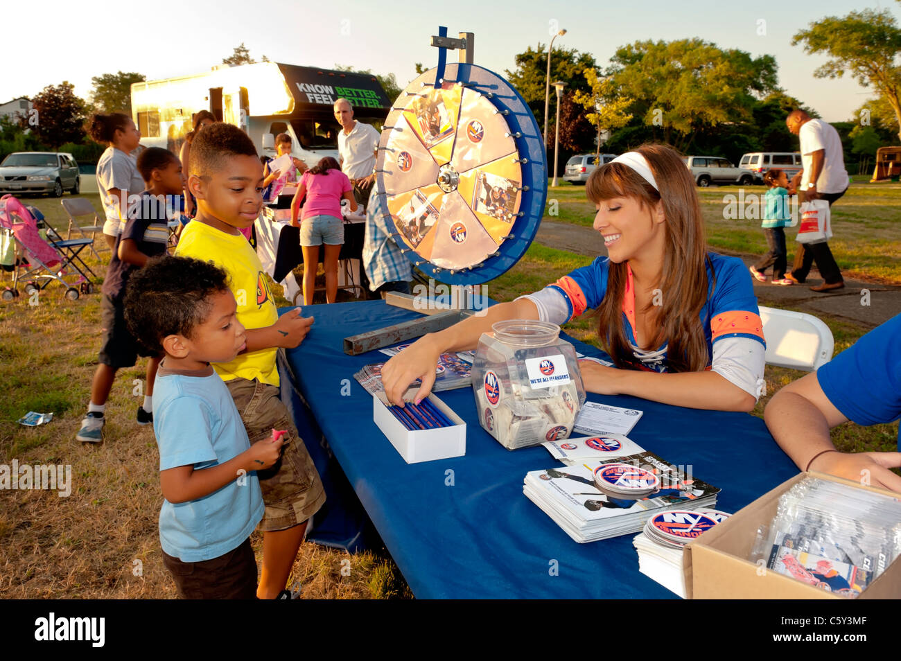 NY Islanders Ice Girl, Christie, giving New York Islanders pencils to two young boys at National Night Out, in Freeport, - Stock Image