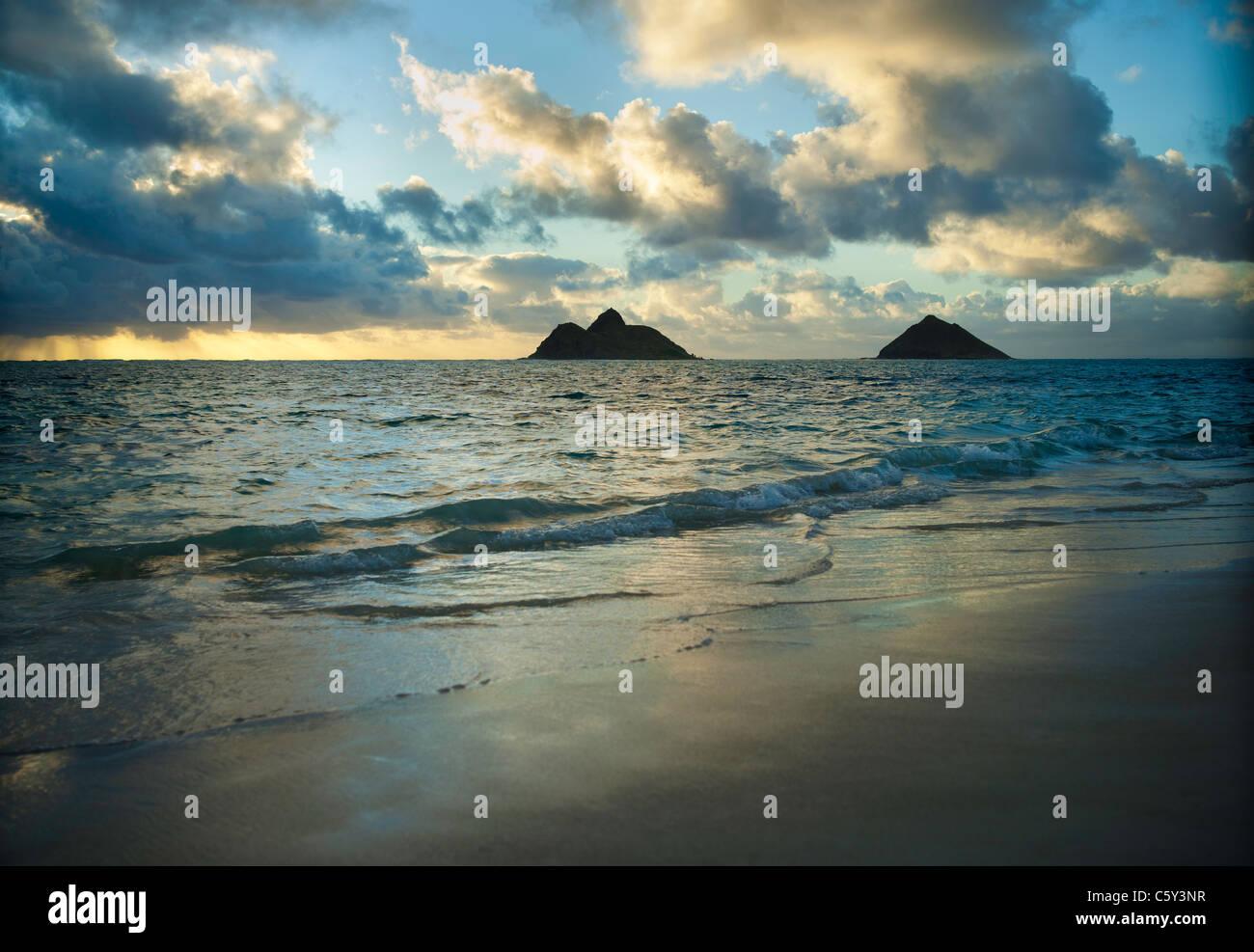 Sunrise at Lanikai Beach on the Windward Oahu coastline, Mokolua Islands in distance. - Stock Image