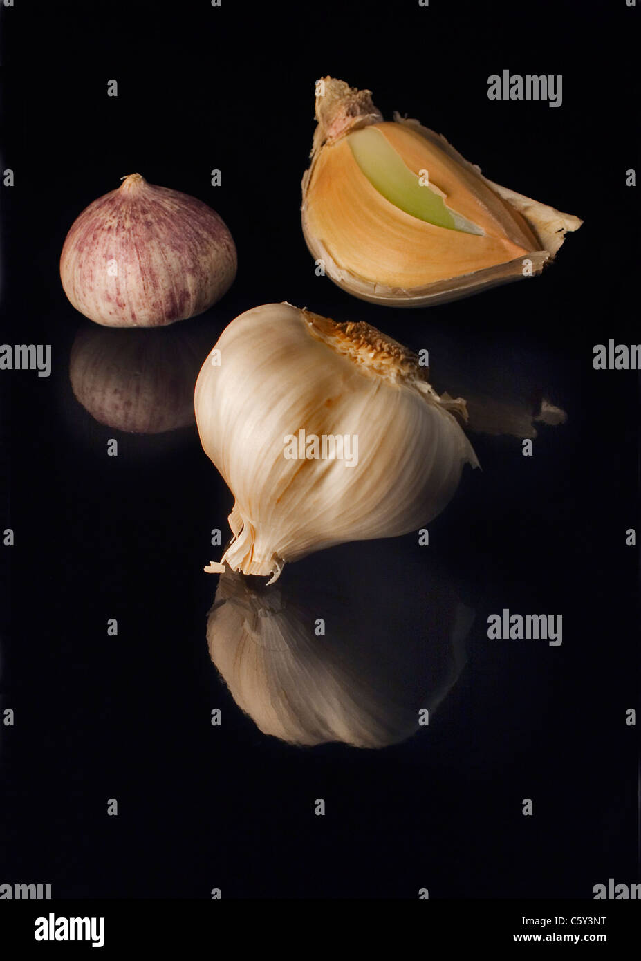 Three types of garlic on a shiny black surface. - Stock Image