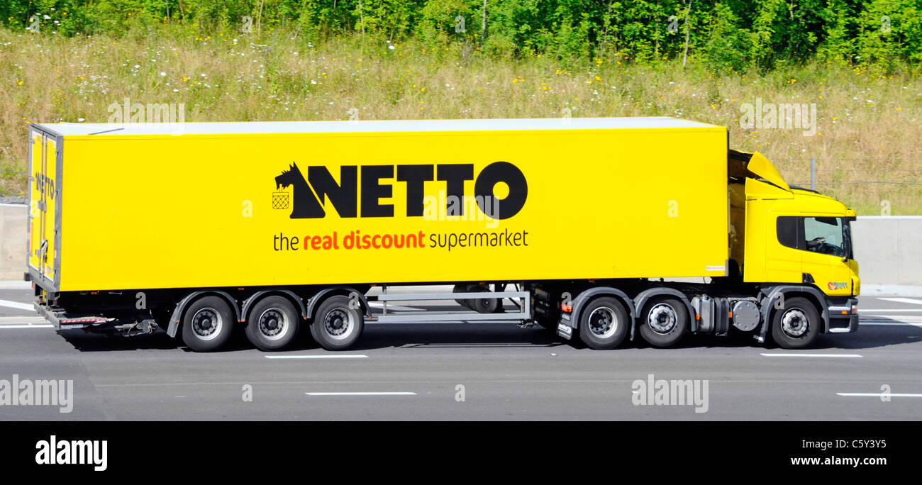 Side view yellow supply chain hgv truck & articulated trailer Netto discount retail supermarket business delivery - Stock Image