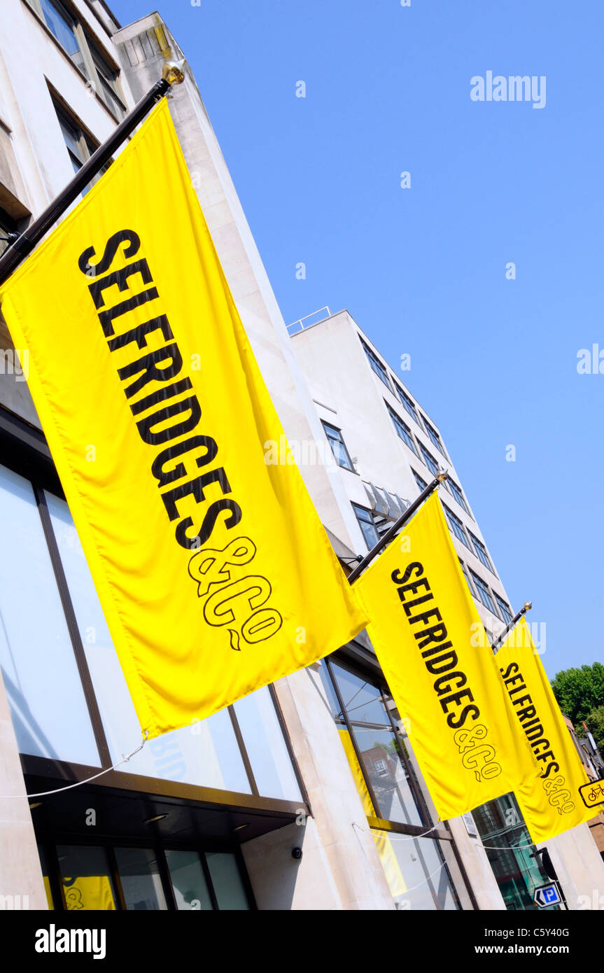 London street scene Selfridges & Co retail department shopping store iconic bright yellow banners West End England - Stock Image