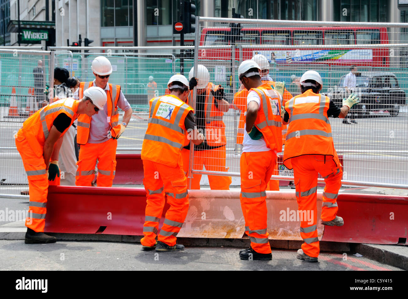 High vis jackets with hard hat & teamwork working together by seven workmen put steel fencing panels across - Stock Image