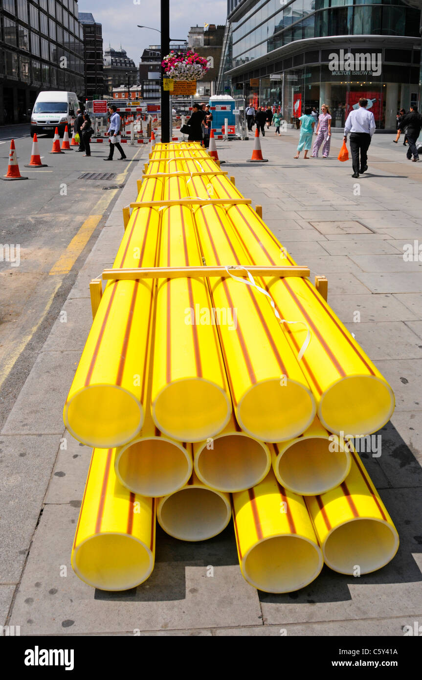 Infrastructure maintenance yellow plastic gas main pipe stacked on pavement to replace aging cast iron underground - Stock Image