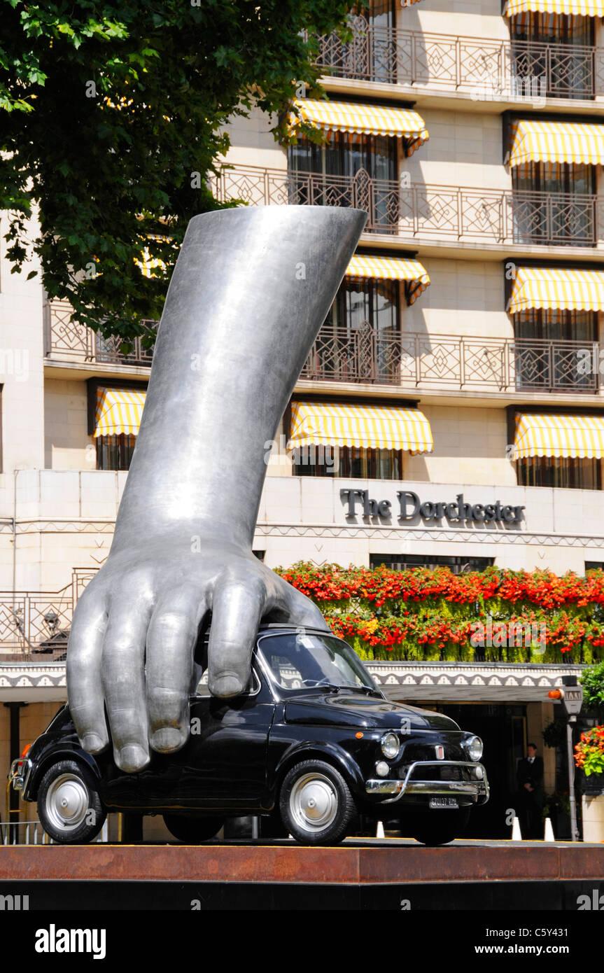 Hand on Vintage Fiat car in modern art sculpture 'Vroom Vroom' by Italian artist Lorenzo Quinn outside Dorchester - Stock Image