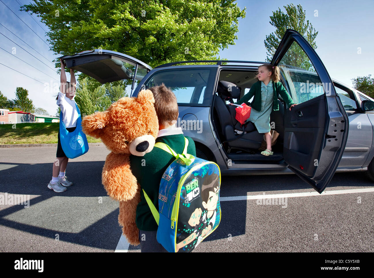 Three young primary age children on their way to school in a people carrier - Stock Image